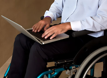 man in wheelchair typing on a laptop computer
